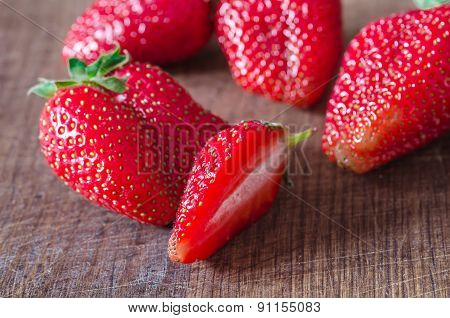 Ripe organic juicy strawberry on wooden table shallow focus