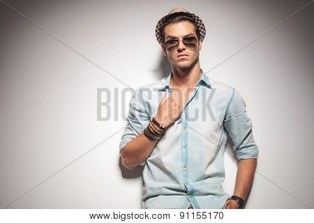 Handsome young fashion man leaning on a studio wall while pulling his shirt.