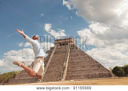 Happy young man jumping of happiness near a pyramid in Chichen Itza, Mexico.
