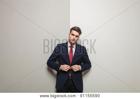 Picture of a young handsome business man leaning on a wall while closing his jacket.