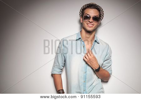 Smiling young fashion man fixing his collar while leaning on a grey wall.