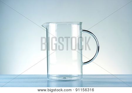 Glass jug on a blue background. Toned image.