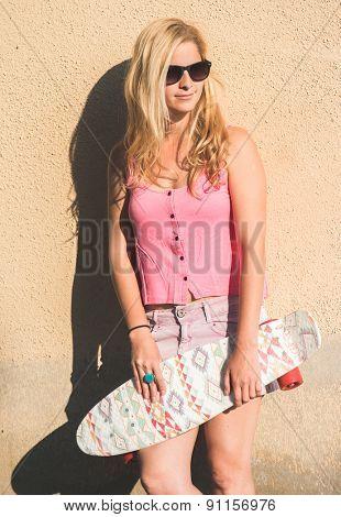 Blonde skateboarder woman posing outdoor