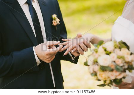 Wedding Rings And Hands Of Bride And Groom