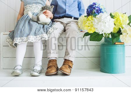 Baby Boy And Girl Sitting On A Wooden Floor