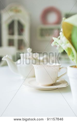 Fine Tea Cup And Kettle On White Table In Kitchen