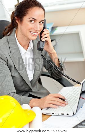Smiling Female Architect Talking On Phone And Using Her Laptop In Her Office