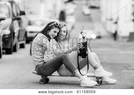 Hipster girlfriends taking a selfie in urban city context - Concept of friendship and fun with new t