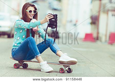 Beautiful young woman posing with a skateboard, fashion lifestyle at sunset