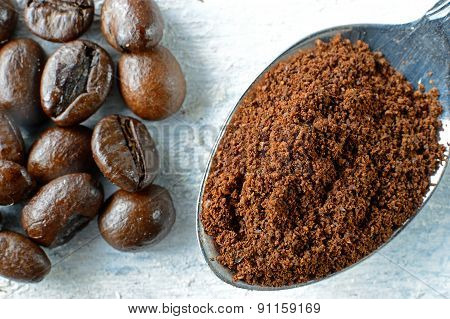 Ground coffee in a spoon and coffee beans