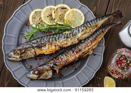 Baked Mackerel Fish With Herbs And Lemon On A Plate
