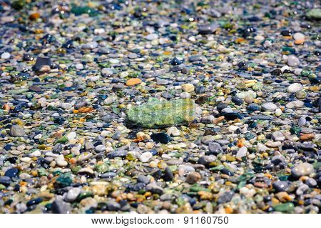 Sea multicolored pebbles, gravel beach in sunlight, selective focus, background