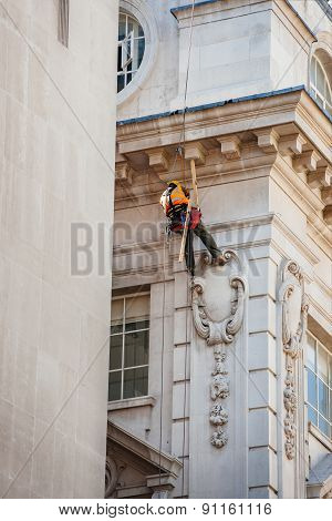 Construction Worker Lowers Himself Into Position To Perform Maintenance High Up Of A Building