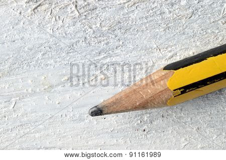 A pencil on a white wooden table.
