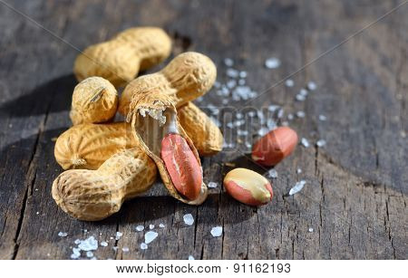 Peanuts in shells  and salt on wood background