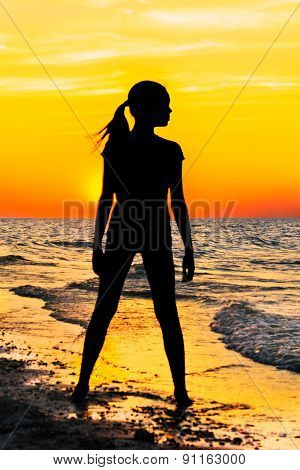 Silhouette Of A Girl On The Beach At Sunset