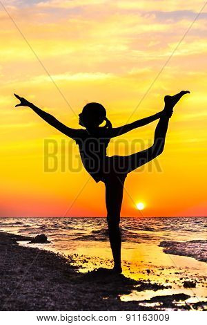 Silhouette Of A Girl In Yoga Pose On The Beach At Sunset