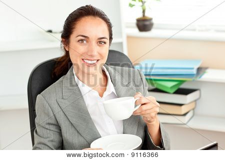 Happy Businesswoman Holding A Cup Of Coffee Sitting In Her Office