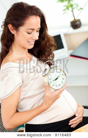 Pregnant Businesswoman Holding An Alarm Clock And Looking At Her Belly In Her Office