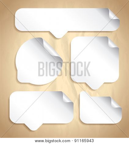 Empty white speech bubble stickers set against old vintage paper backdrop