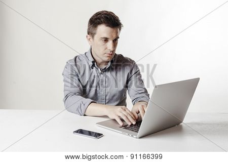Close up image of multitasking business man using a laptop and mobile phone