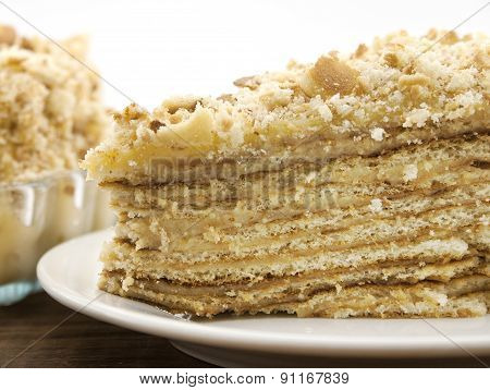Layered Cake Slice With Nut On Plate, On Wooden Table, Dark Background. Selective Focus