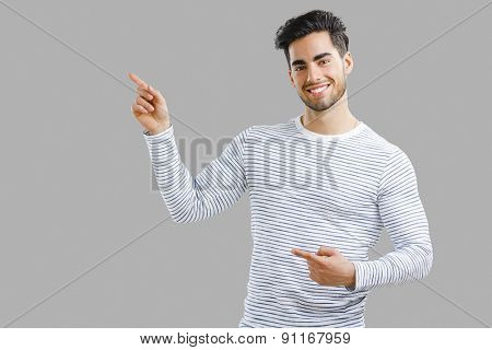 Handsome young man holding and pointing to a small chalkboard, isolated over a white background