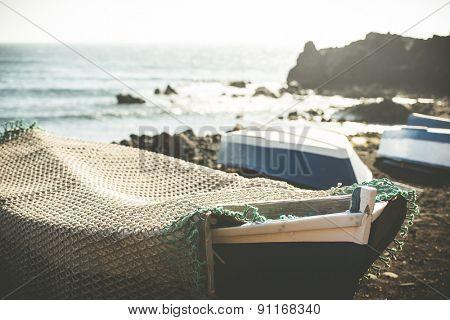boat on a sandy shore on rocky coastline background