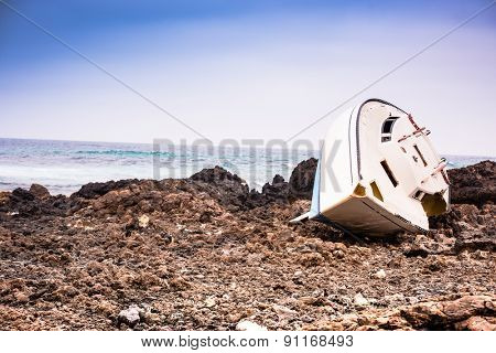 white boat on a stony shore by the sea