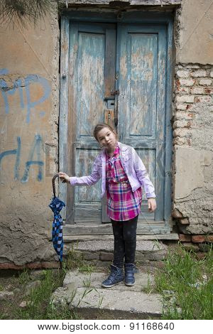 Little girl with an umbrella in her hands standing at the door of her house