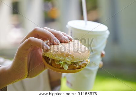 woman eating hamburger and cocktail