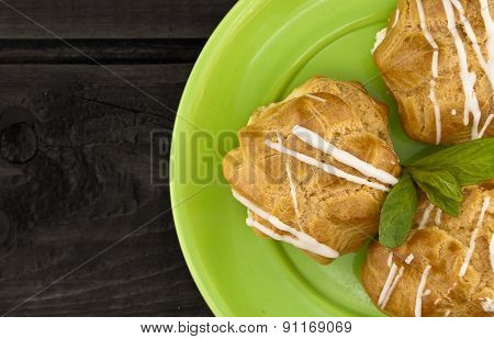 Eclair On Green Plate, On Dark Rustic Wooden Background, Top View.