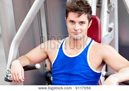 Self-assured Young Man Using A Bench Press