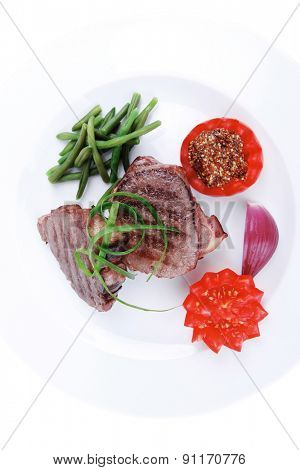 roasted beef meat strips steak on white ceramic plate with sweet pea and tomatoes isolated over white background