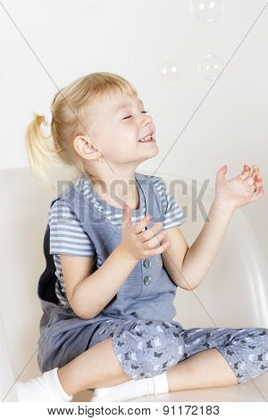 little girl sitting on armchair and playing with bubbles