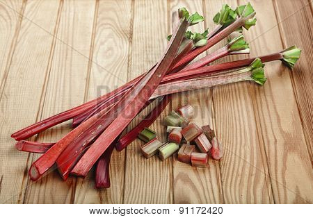 Rhubarb stalks and chops on wooden table