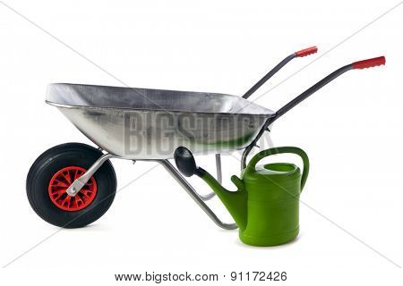 Empty new galvanized wheelbarrow and green plastic watering can isolated on white background