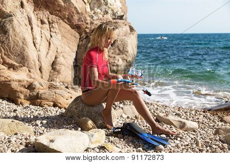 Sexy Diver Girl Sitting On The Cliff Of The Rocky Beach And Preparing Her Dive.