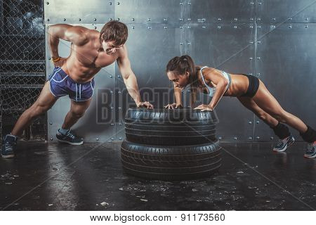 Sportswomen. Fit sporty woman and man doing push ups on tire strength power training concept crossfi