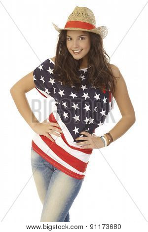 Beautiful young woman posing in American flag t-shirt and straw hat, hand on hip, smiling happy.