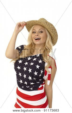 Pretty blonde American woman posing in American flag t-shirt and straw hat, smiling.