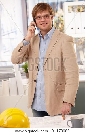 Happy caucasian architect talking on phone at office pointing at table. Wearing glasses, looking up, hardhat.