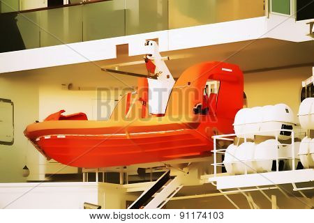 Orange life boat attached to a cruise ship