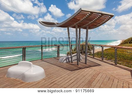 Wooden viewpoint overlooking Mediterranean sea under blue sky with white clouds in Israel.