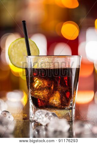 Glass of cola drink on bar counter with ice cubes