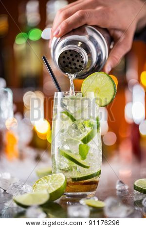 Mojito cocktail drink on bar counter with barman holding shaker on background