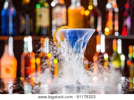Martini drink with dry ice smoke effect, served on bar counter with blur bottles on background