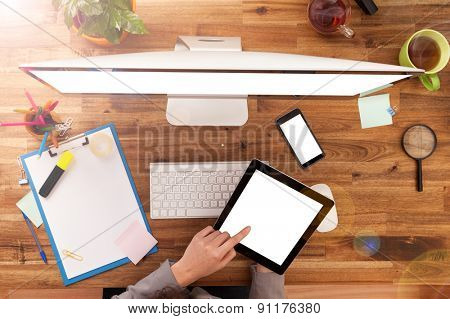 Young woman working with tablet and modern PC placed on wooden desk with blank screen for text. Shot from aerial view