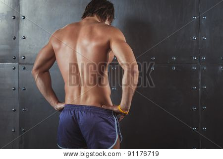 Athletic young man showing muscles of back Rear view strong male. Fitness male model standing near w