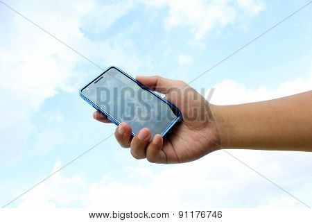 Hand Holding Smart Phone on The Sky Background